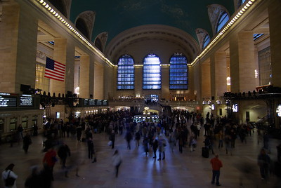 The Main Concourse is the center of Grand Central. The space is cavernous and usually filled with bustling crowds. The ticket booths are here, although many now stand unused or repurposed since the introduction of ticket vending machines. The large American flag was hung in Grand Central Terminal a few days after the attacks on the World Trade Center on September 11, 2001. The unusual ceiling of the Main Concourse is described below. The main information booth is in the center of the concourse. This is a perennial meeting place, and the four-faced clock on top of the information booth is perhaps the most recognizable icon of Grand Central. Each of the four clock faces are made from opal, and both Sotheby's and Christie's have estimated the value to be $10m-$20m. Within the marble and brass pagoda lies a secret door that conceals a spiral staircase leading to the lower level information booth.  Outside the station, the clock in front of the Grand Central facade facing 42nd Street contains the world's largest example of Tiffany glass and is surrounded by sculptures carved by the John Donnelly Company of Minerva, Hercules and Mercury. For the terminal building French sculptor Jules-Alexis Coutan created what was at the time of its unveiling (1914) considered to be the largest sculptural group in the world. It was 48 feet (14.6 m) high, the clock in the center having a circumference of 13 feet (4 m).  The upper level tracks are reached from the Main Concourse or from various hallways and passages branching off from it.