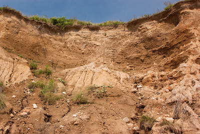 Factor which cause rates of erosion to vary is a combination of several different things, including the amount and intensity of precipitation, the texture of the soil, the gradient of the slope, ground cover from vegetation, rocks, land use, and possibility of erosion from speed of a stream. The first factor, rain, is the agent for erosion, but the degree of erosion is governed by other factors.  The first three factors can remain fairly constant over time. In general, given the same kind of vegetative cover, you expect areas with high-intensity precipitation, sandy or silty soils and steep slopes to be the most erosive. Soils with a greater proportion of clay that receive less intense precipitation and are on gentle slopes tend to erode less. But here, the impact of atmospheric sodium on erodibility of clay should be considered.