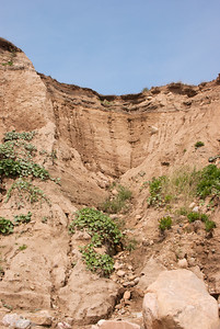 Erosion is distinguished from weathering, which is the decomposition of rock and particles through processes where no movement is involved, although the two processes may be concurrent.  Erosion is an intrinsic natural process but in many places it is increased by human land use. Poor land use practices include deforestation, overgrazing, unmanaged construction activity and road or trail building. However, improved land use practices can limit erosion, using techniques like terrace-building and tree planting.