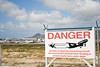 """The """"Danger"""" sign, with the airport in the background"""