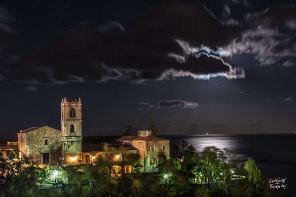 Moon slips behind the clouds, shining over the Ionian Sea