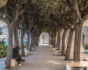 A shaded sidewalk on on Piazza Giuseppe Garibaldi, just before the old, walled part of Polignano.