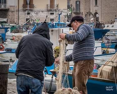 A couple of fisherman sorting out the fishing nets.