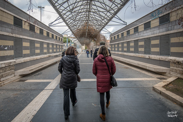 Nancy and Denise heading towards Vatican City, ducking under an arbor off Via Cipro