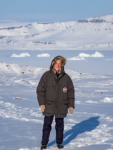 Claire in front of Wolstenholme Fjord and icebergs in sea ice