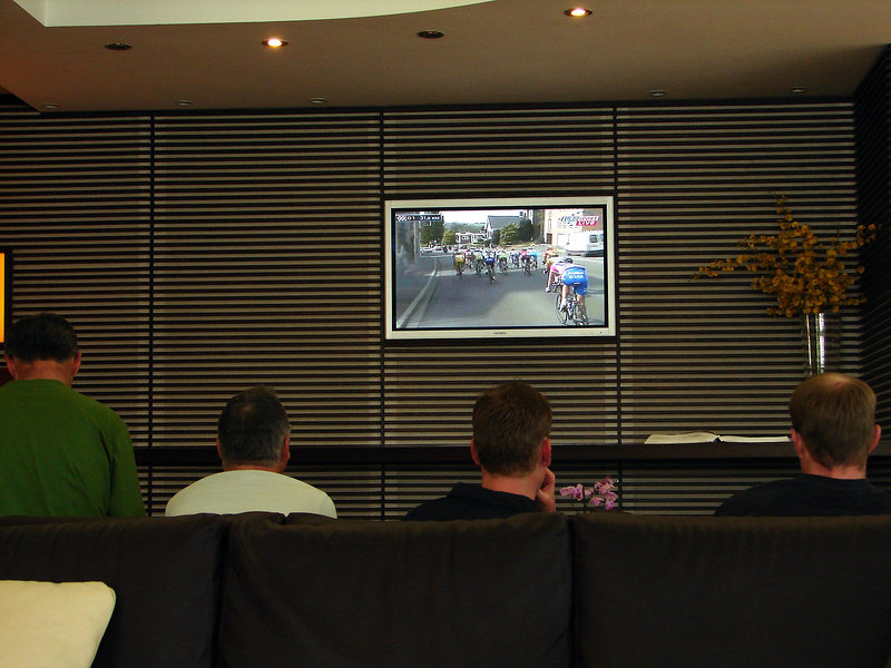 the cyclists watching a race on the plazzzma tv in the hotel.