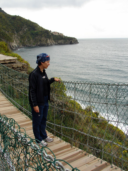 Michelle on a new suspended bridge. the old one recently got nuked by a landslide from the impossibly steep cliffs directly beside and uphill.