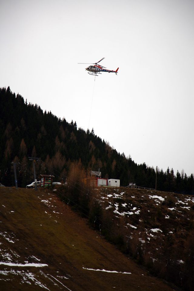 The helicopter lifting snowblowers to the course