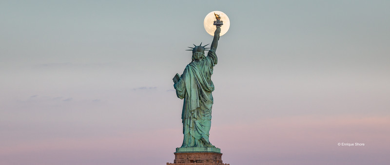 An almost full moon rises in front of the Statue of Liberty in New York
