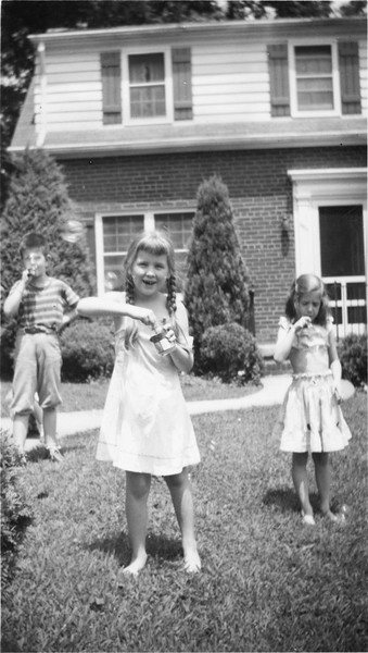 Judy blowing bubbles. May be Ann Hannowell behind her.
