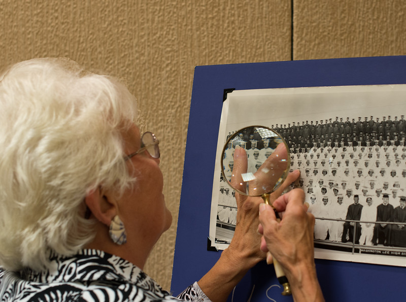 Sue Rogers Frank searches for friends in the 1959 class picture after the Ladies' Tea.
