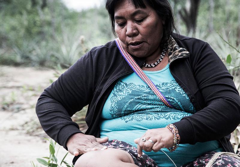 Las hebras del chaguar las trabajan sentadas en el suelo contra sus rodillas y logran el hilo. /// They work the chaguar strands against her knees, sitted on the floor, and get the yarn.