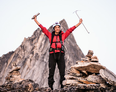 Classic summit pose. Holding up a summit register and a mountaineering axe on top of Crescent Towers (Bugaboo Spire in the background). Bugaboo Provincial Park, British-Columbia.