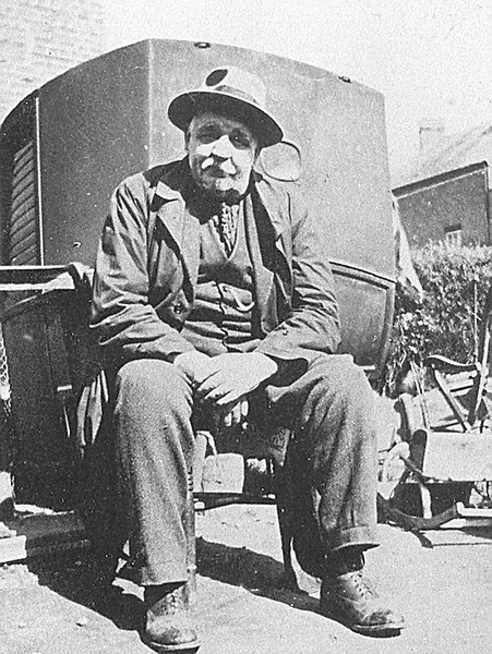 "<center><font size=3><u> - Mr Thomas Pether - </u></font> (BS0340)  Mr Thomas Pether in about 1932 seated behind an old wheel-less horse drawn carriage that had remained for a long period in the area behind the White Hart Hotel.  Mr Pether lived in the house between the hotel and the Castle Farmhouse.  It was called ""Fairlight"".  It became unsafe, and was demolished in about 1934, eventually to become the site of the new house there in 2000.  The carriage was moved in to his garden, and was used as a child's playhouse. (Source, Mr Alan Hewett).  </center>"