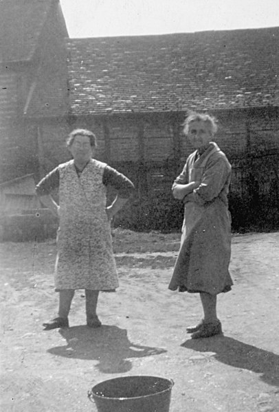 "<font size=3><u> - Two Ladies in  Birmingham Yard - </u></font> (BS0276)  Mrs Field on left.   Mrs Painting on the right.   The building was the wheelwright's shop.  He was Mr Charlie Lewendon who lived at the Farmer's Man.  The famous walnut tree is out of view to left of photo – outside the blacksmith's shop.   There were two ""ironers"" in the yard-one outside the blacksmith's shop and one outside one of the cottages. They were used to shape the iron tyres for waggon wheels.  See BS1122 below."