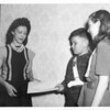 The lady was visiting from Guatemala. I am wearing a school crossing guard belt so this is likely about 1947. The girl on the right is a neighbor girl, Nancy Miller.  I have no recollection of what we might have been giving the lady. ~ Paul Valentine