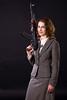 smiling businesswoman wtith submachine gun