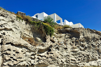 House perched on a sand cliff in Oia - Santorini, Greece.