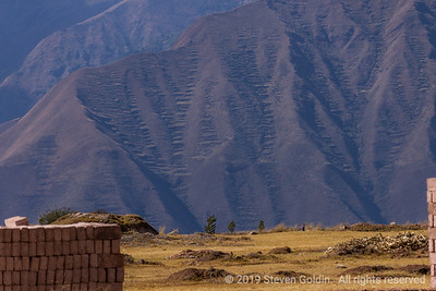 Adobe brick stacks and agricultural terraces on the mountain.