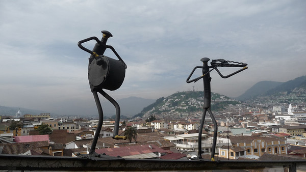 Right underneath violinist's elbow, checkout the Virgin of El Panecillo on the hill top in the background.