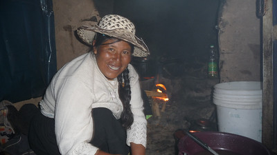 Our host family mother, Epiphinea, cooking in the tiny hut that serves as both kitchen and dining room.  Notice the fire and cast iron pots - that's the stove.  The buckets to the right make for the sink, refrigerator, and garbage.  Amazing how much they do with so little.