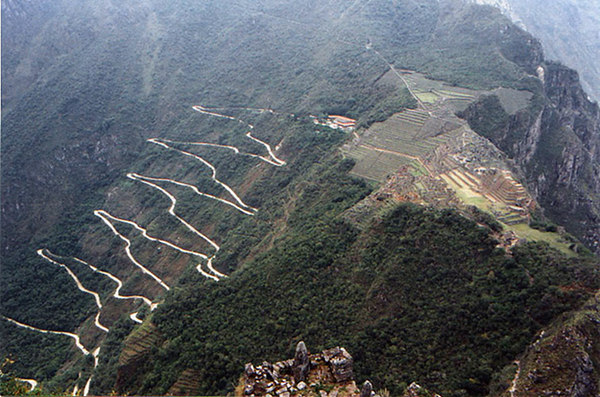"""This photo shows the amazing road up from the valley to the historical site. You can also see the end of the Inca Trail at the top. <i>[Not my picture: I found it on a Traveladdicts webpage no longer available. But see <a href=""""http://blog.tourvia.me/how-to-get-to-machu-picchu/"""" target=""""_blank"""">Tourvia</a> - scroll down the page.]</i>"""