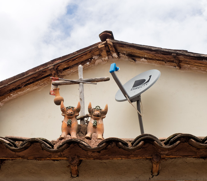 It is very common for homes in this part of Peru to have two bulls and a cross on the roof -- it is believed to provide protection for the home.  Here, the bulls and cross share their space with something a bit more modern.