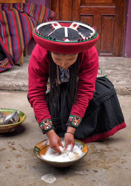 "A weaver demonstrates how raw wool is washed in a solution of water with suds from a grated ""saqta"" root -- a natural detergent."