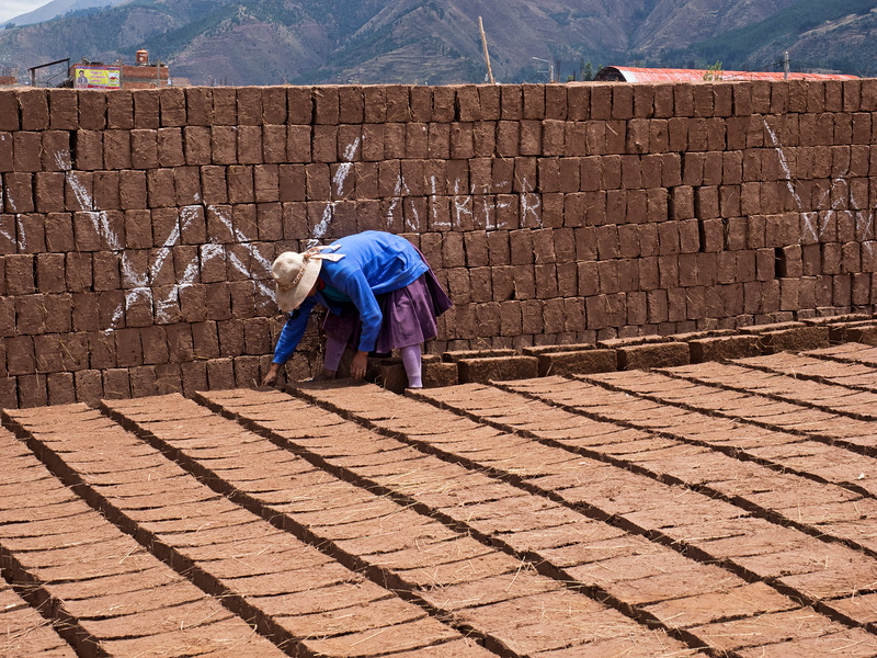 After a while, she turns the bricks so they can dry on both sides.
