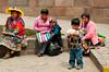 Peruvian ladies in traditional dress with their children in Cusco, Peru, South America.