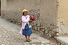 A lady carrying flowers in traditional peruvian dress walking on the street in Ollantaytambo, Peru, South America.