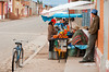 A village street with small kiosks and peruvians in traditional dress in rural Peru, South America.