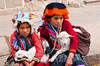 Peruvian children in traditional dress with their pet lambs in the Pisac market, Urubamba Valley, Peru, South America.