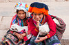 Peruvian children in traditional dress with lambs in the  Pisac market, Urubamba Valley, Peru, South America.