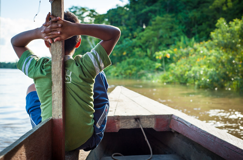 A boy sits at the front of a boat to help with navigating, Iquitos, Peru, South America