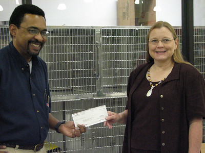 Basil Cousins, Operations Manager of Tallahassee PetSmart, presents a $25,000 grant check to Melissa Abernathy, Program Director of the Leon County Humane Society.