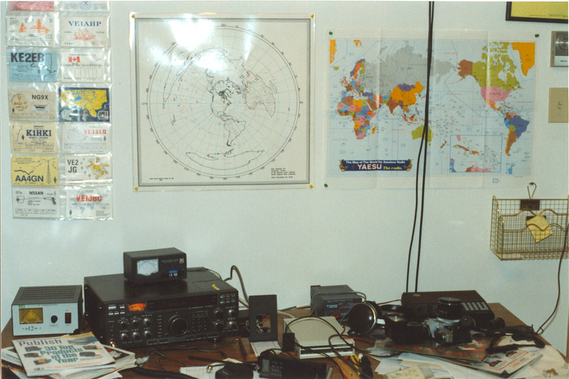 Study 32 Revillon Road South in Moosonee. c1994 December. VE3KBL amateur ratio station. QSL cards, maps on the wall, Yaesu FT-990, HT, scanner and digital equipment on desk along with camera / flash and power supplies.