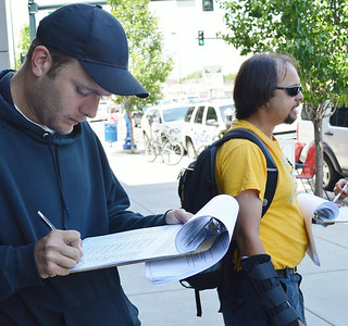 Young man signs petition on clipboard, in background petitioner holds clipboard for person signing.