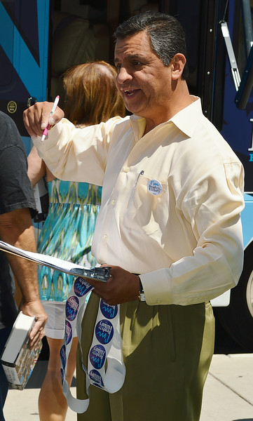Man holding clipboard and Hillary Clinton buttons gestures with hand.