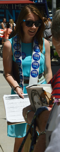 Young woman with Hillary Clinton stickers around her neck shows paper on clipboard to woman holding Hillary Clinton book.