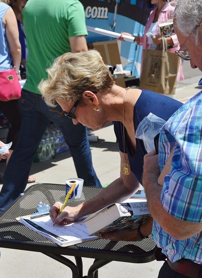 Woman leans over to sign paper on clipboard on table.