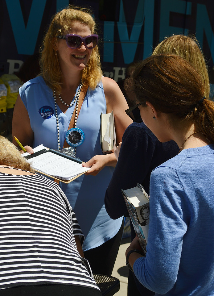 Young woman wearing Hillary Clinton buttons shows paper on clipboard to woman holding Hillary Clinton book.