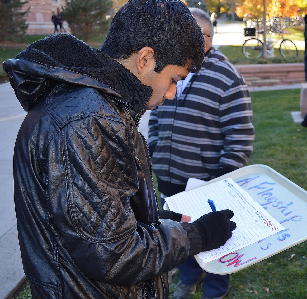 Young man signing a petition at union rally.