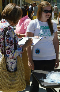 Woman signing paper on clipboard,  young woman wearing Hillary Clinton button standing next to her.