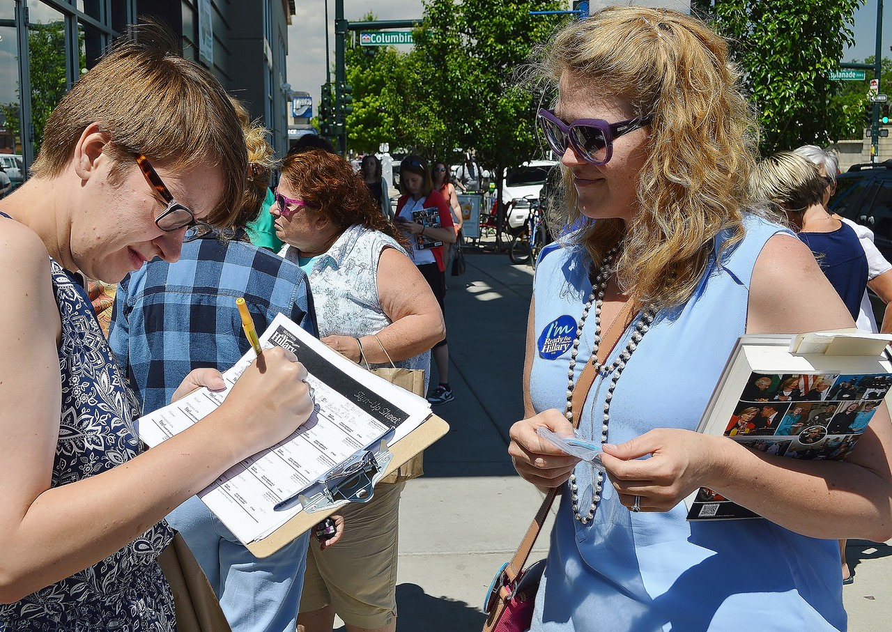 Woman signing paper on clipboard, volunteer wearing Hillary Clinton button and holding book, looks on.