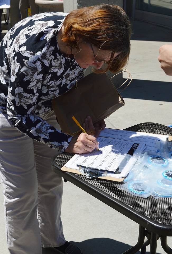 Woman leans over to sign a paper on clipboard on a table.