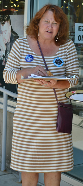 Woman wearing Hillary Clinton button, holding clipboard.