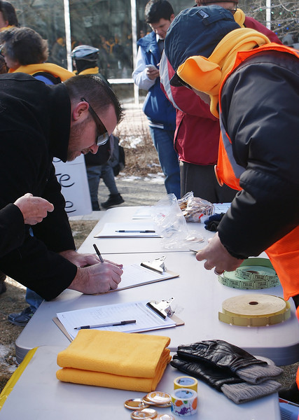 Rooftop solar energy supporters sign petitions against utility company Xcel Energy's metering policies.