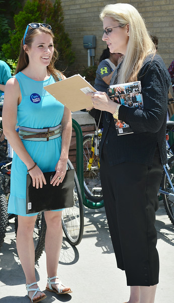 wearing Hillary Clinton button smiles as another woman holding Clinton book signs paper on clipboard.