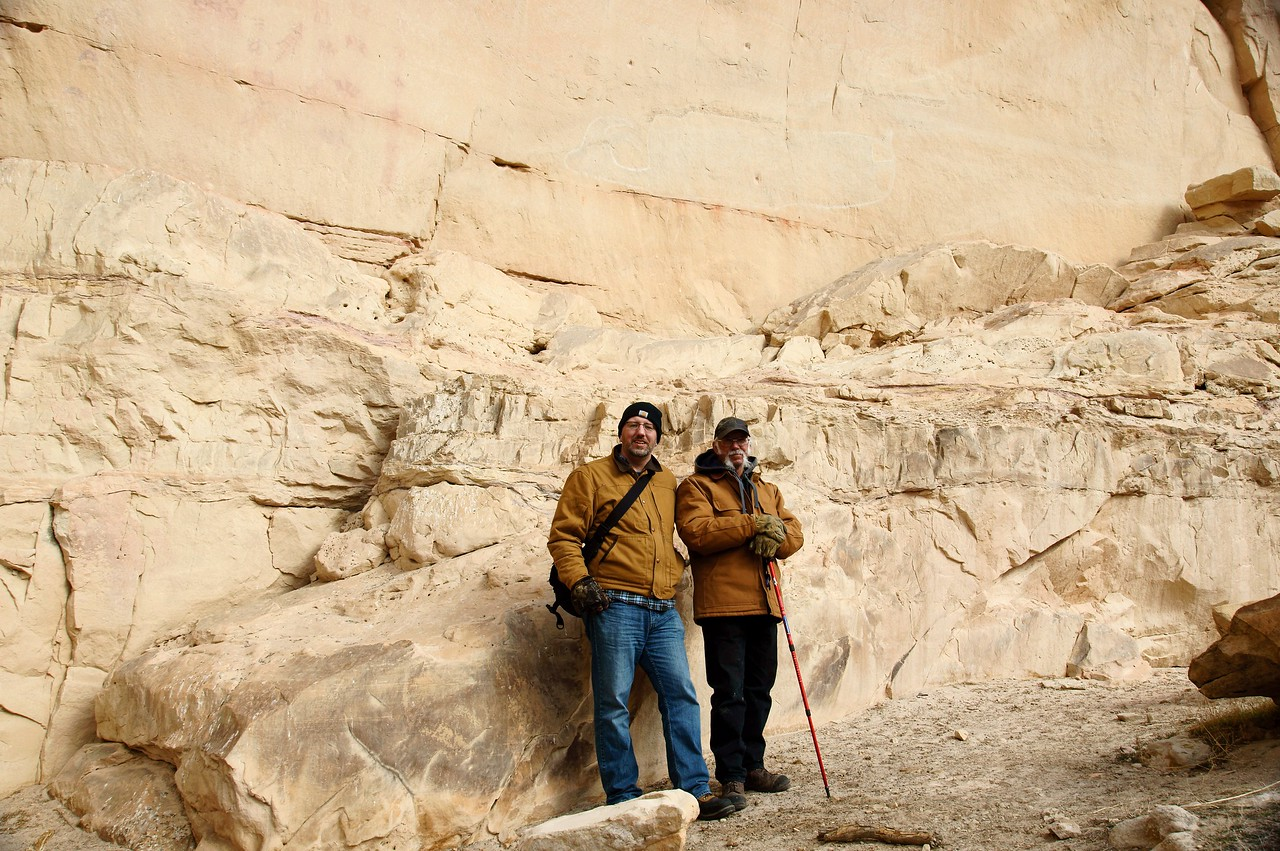 Dad and I standing next to the panel wall.  The canyon floor has lower over time, which is why the pictographs appear much higher than us.